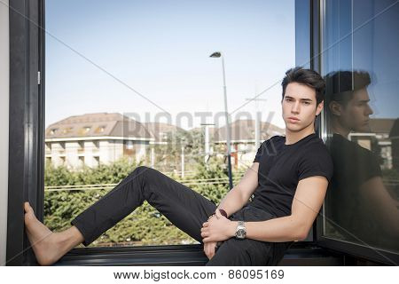 Handsome Young Man Sitting On Open Window Sill