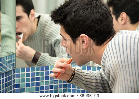 Headshot Of Attractive Young Man Brushing Teeth