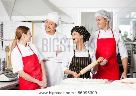 Cheerful male and female chefs conversing while preparing pasta in commercial kitchen