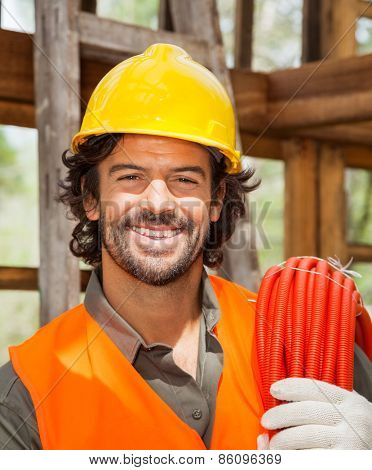 Portrait of confident male worker with pipe in wooden cabin at construction site