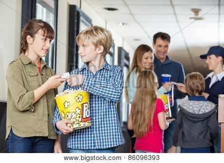 Brother giving movie tickets to sister at cinema with family and worker in background