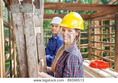 Portrait of happy female construction worker with male colleague in wooden cabin at site