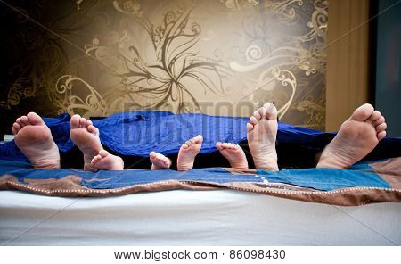Four pairs of legs of the happy family in bed - father, mother and children