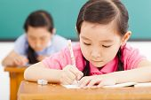 image of classroom  - children in classroom with pen in hand - JPG