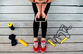 pic of roping  - Sporty woman holding phone with empty screen sitting on the sunbed with jump rope - JPG