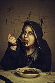 stock photo of bloody  - Bloody young girl in hood having a breakfast - JPG