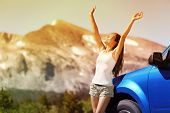 stock photo of road trip  - Happy free woman next to car relaxing on summer road trip adventure travel with open arms up showing freedom - JPG