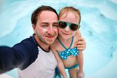 stock photo of swimming pool family  - Happy family father and his adorable little daughter at outdoors swimming pool making selfie - JPG