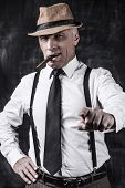 foto of suspenders  - Serious senior man in hat and suspenders smoking cigar pointing you while standing against dark background - JPG