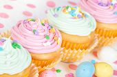 stock photo of easter candy  - Pastel Easter cupcakes with candy and sprinkles shallow depth of field - JPG