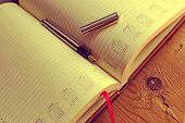 stock photo of scribes  - Open diary with one fountain pen in it placed on a wood table - JPG