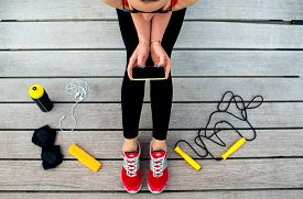 image of roping  - Sporty woman holding phone with empty screen sitting on the sunbed with jump rope - JPG
