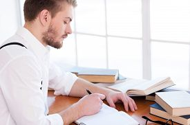 pic of suspenders  - Side view of confident young man in shirt and suspenders writing something in note pad while sitting at the table with book laying on it - JPG
