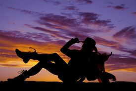 foto of western saddle  - A silhouette of a cowgirl taking a break and leaning back on her saddle - JPG