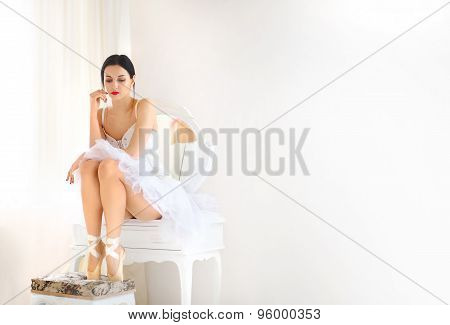 Beauty brunette ballerina in room, wearing  costume, ballet skirt and corset