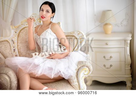 Beauty brunette ballerina in room, wearing  costume, ballet skirt and corset