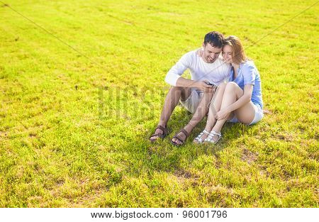 Lifestyle Concept: Caucasian Couple Sitting Embraced Together On The Grass Outdoors With Palmtop Han