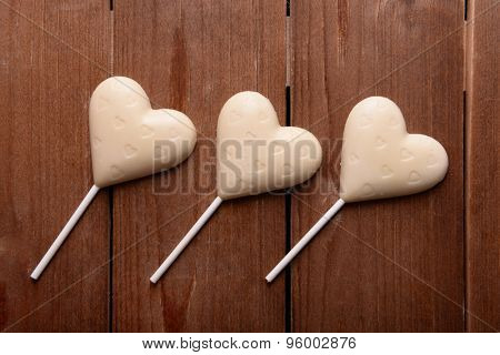 Chocolate candies in shape of hearts on wooden background