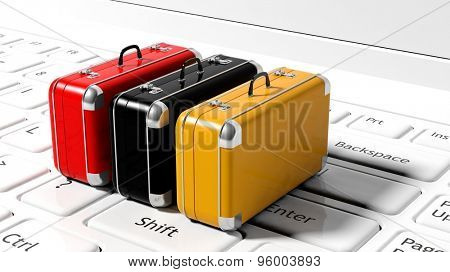 Colorful suitcases on white laptop keyboard
