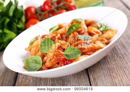 Pasta with tomato sauce and basil on table close up