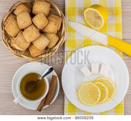 Biscuits In Basket, Hot Tea, Lemon, Sugar Cubes And Knife
