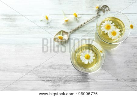 Glass of chamomile tea with chamomile flowers on color wooden background