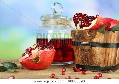Pomegranate seeds and juice on wooden table on light blurred background