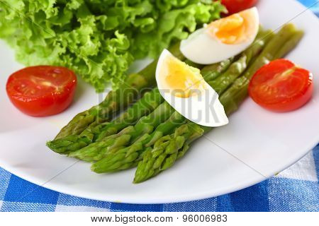 Plate of dietary salad with boiled asparagus and egg, closeup