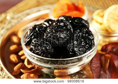 Prunes and other dried fruits in glass with grape leaves saucers, closeup