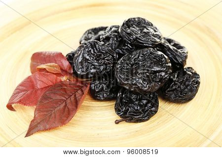 Pile of prunes with leaves on wooden background