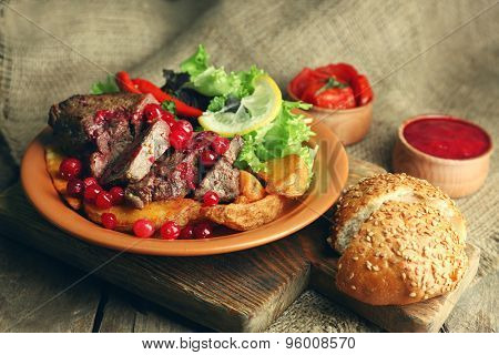 Tasty roasted meat with cranberry sauce, salad and roasted vegetables on plate, on sackcloth background