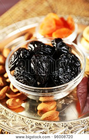 Pile of prunes in glass saucers with grape leaves, closeup