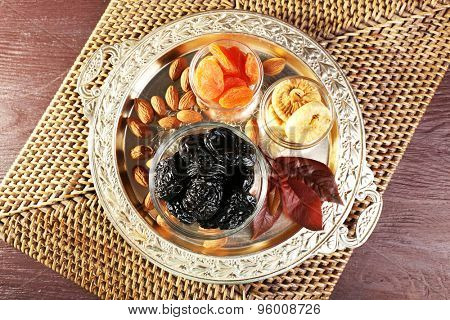 Prunes and other dried fruits in glass saucers with grape leaves on metal tray and wicker mat, top view