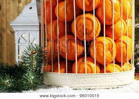 Tangerines in decorative cage with Christmas decor, on wooden background
