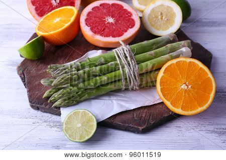 Fresh asparagus and grapefruit on cutting board on color wooden background