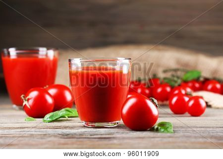 Glasses of tomato juice with vegetables on wooden table close up