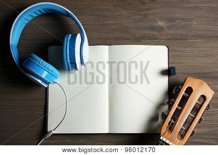 Music recording scene with classical guitar, notebook and headphones on wooden table, closeup
