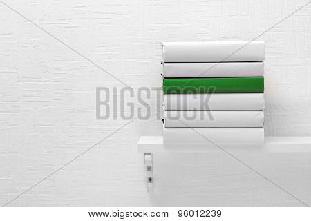Blank books and green one on shelf on white wallpaper background