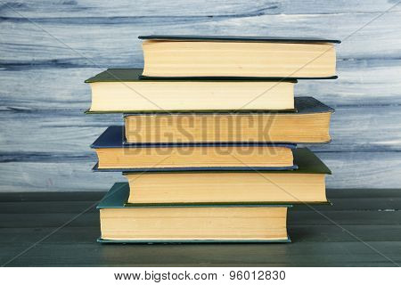 Stack of books on wooden table on blue wooden wall background