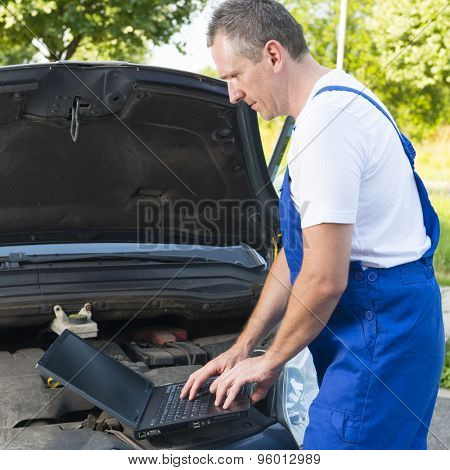 Mobile car service engineer checking car with his laptop on the road