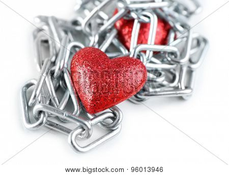 Two red hearts with metal chain isolated on white