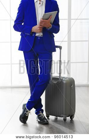 Business man with suitcase and tablet in hall
