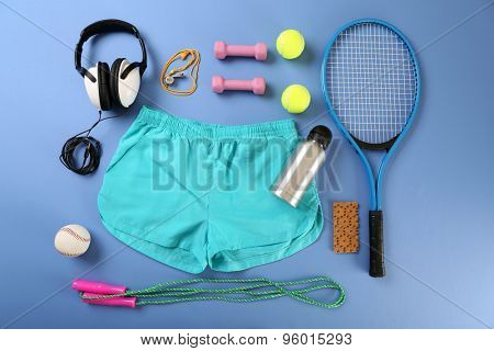 Sports equipment and shorts on color table, top view
