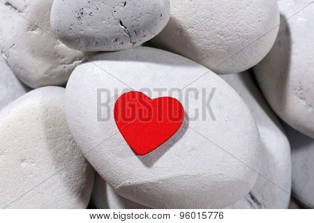 Red heard over pebbles background
