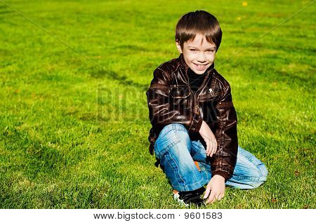 Little boy sitting Down on thegrass