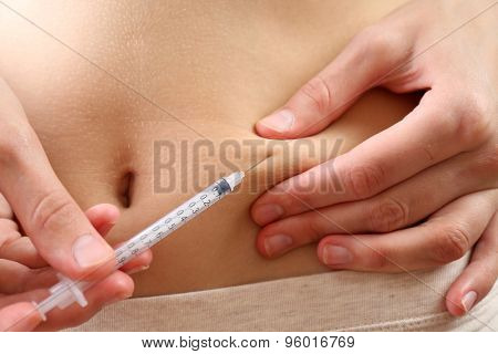 Woman doing shot in stomach close up