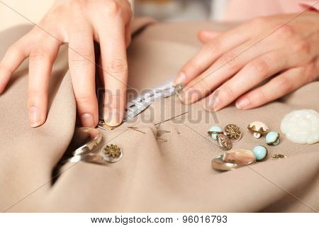 Closeup hands of seamstress at work with cloth fabric