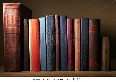 Old books on shelf, close-up, on dark wooden background