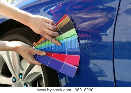 Female hands with paint samples choosing color for painting car, closeup
