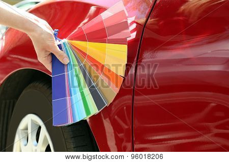 Female hand with paint samples choosing color for painting car, closeup